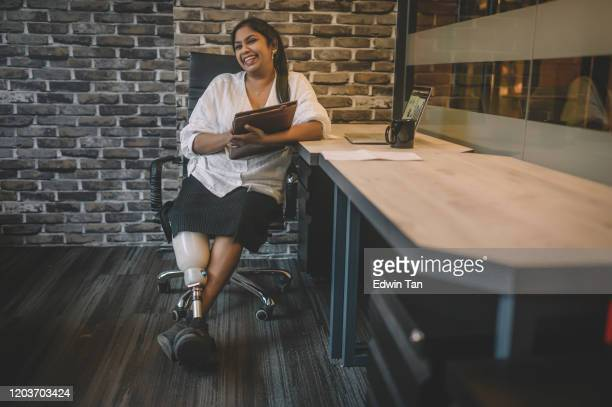 a portrait of an asian indian white collar worker with prosthetic leg sitting at her workstation with toothy smile confidence holding her digital tablet with leg crossed on ankle - disabilitycollection stock pictures, royalty-free photos & images