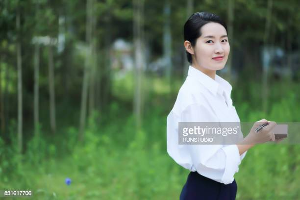 a portrait of  business woman taking a notebook - 白い服 ストックフォトと画像