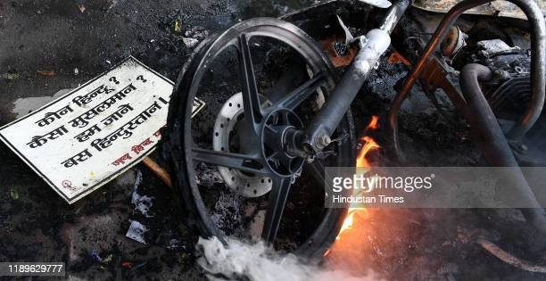 a poster next to a burning motorbike during an anti Citizenship Amendment Act and National Register of Citizens protest at Parivartan Chowk area on...