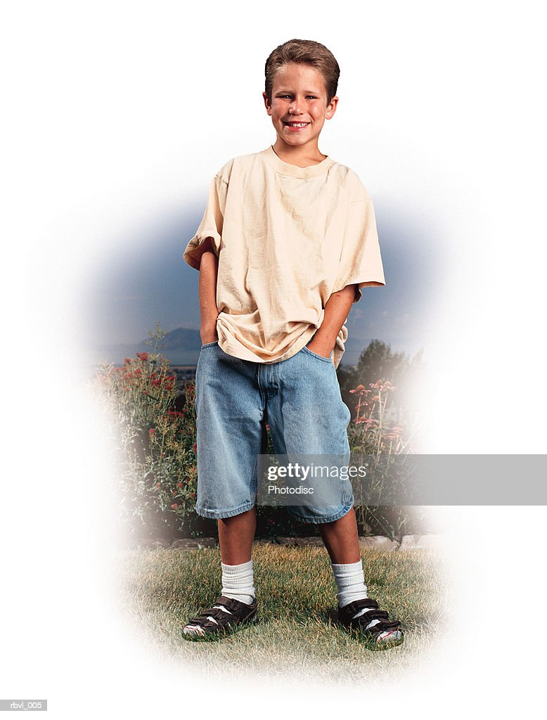 a preteen caucasian boy in a yellow t-shirt and blue shorts is standing with his hands in his pockets smiling at the camera : Foto de stock