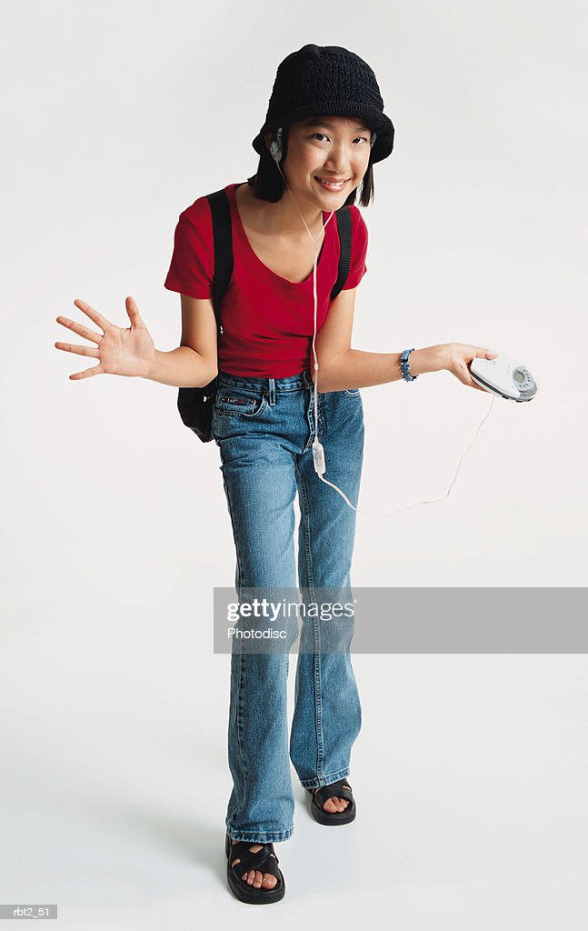 a pretty asian preteen girl wearing a red teeshirt and blue jeans has on a black hat and is leaning towards the camera as she wears a backpack and spreads her arms while listening to a walkman stereo : Foto de stock