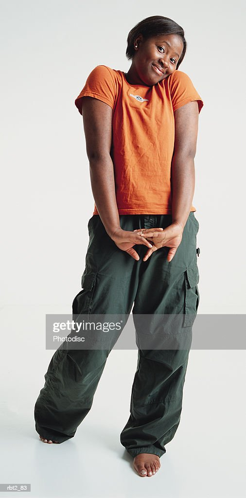 a pretty barefoot african american teenage girl wearing an orange teeshirt shrugs her shoulders and cocks her head while smiling shyly : Foto de stock