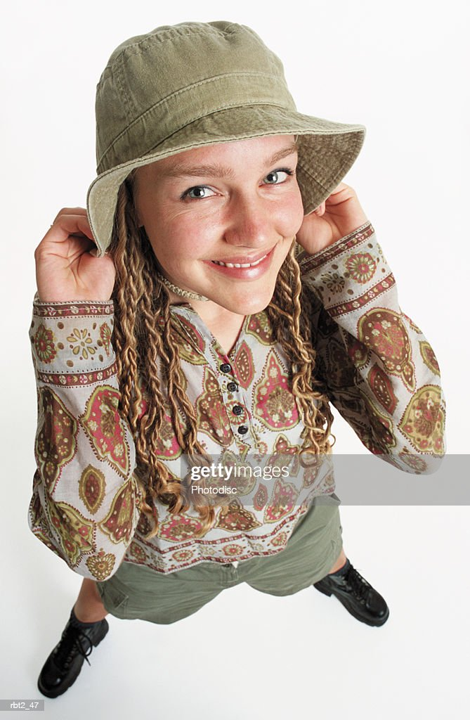 a pretty caucasian teenage girl with long blonde dreadlocks is tugging a khaki hat over her head and wearing a paisley blouse and smiling up into the camera : Foto de stock