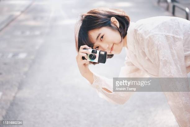 a pretty girl with a camera - camera girls stock photos and pictures