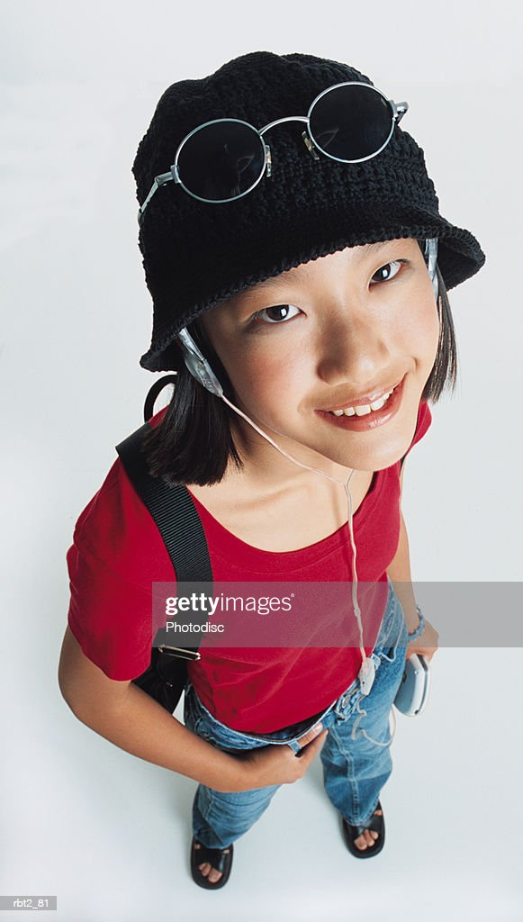 a pretty preteen asian girl with sunglasses perched on her knit hat is wearing a red teeshirt and holding her walkman as she listens to the earphones and looks up at the camera : Foto de stock