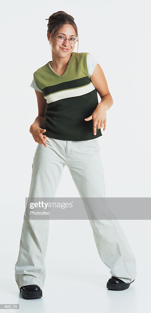 a pretty teenage girl wearing a green vest and white jeans has her hair in a bun and smiles at the camera gesturing with her hands near her hips : Foto de stock