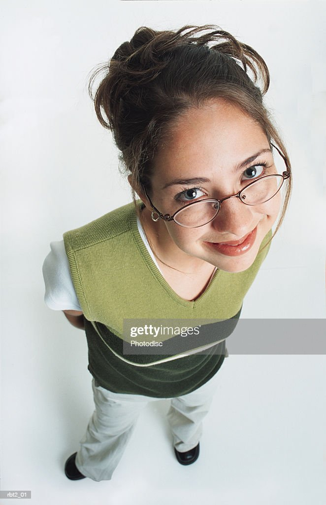 a pretty teenage girl wearing glasses and a green vest smiles shyly up at the camera : Stockfoto