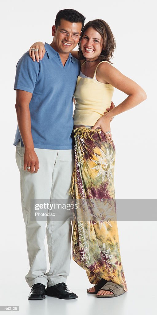 a pretty young caucasian woman in a tank top and tye dyed skirt stands with her arm around a handsome young latino man in white slacks and a blue polo shirt : Foto de stock