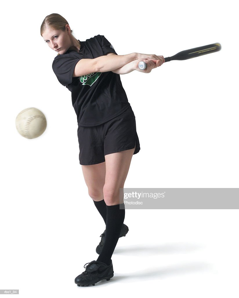 a pretty young caucasian woman is wearing a black softball uniform and swinging her bat after hitting a ball : Foto de stock