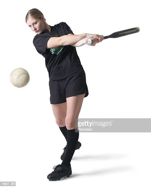 a pretty young caucasian woman is wearing a black softball uniform and swinging her bat after hitting a ball - 野球バット ストックフォトと画像