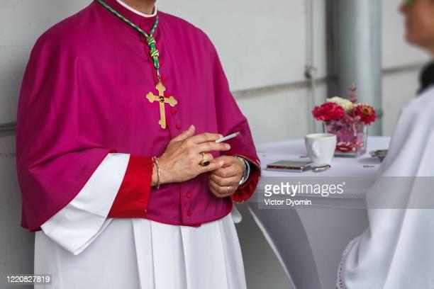 a priest in a purple mantle with a cigarette in his hand - ongebruikelijk stockfoto's en -beelden