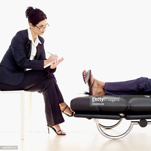 a psychiatrist listening to a patient and taking notes - psychiatrist's couch stock pictures, royalty-free photos & images