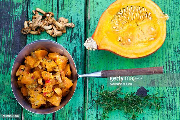 a pumpkin stew on a painted green wooden background