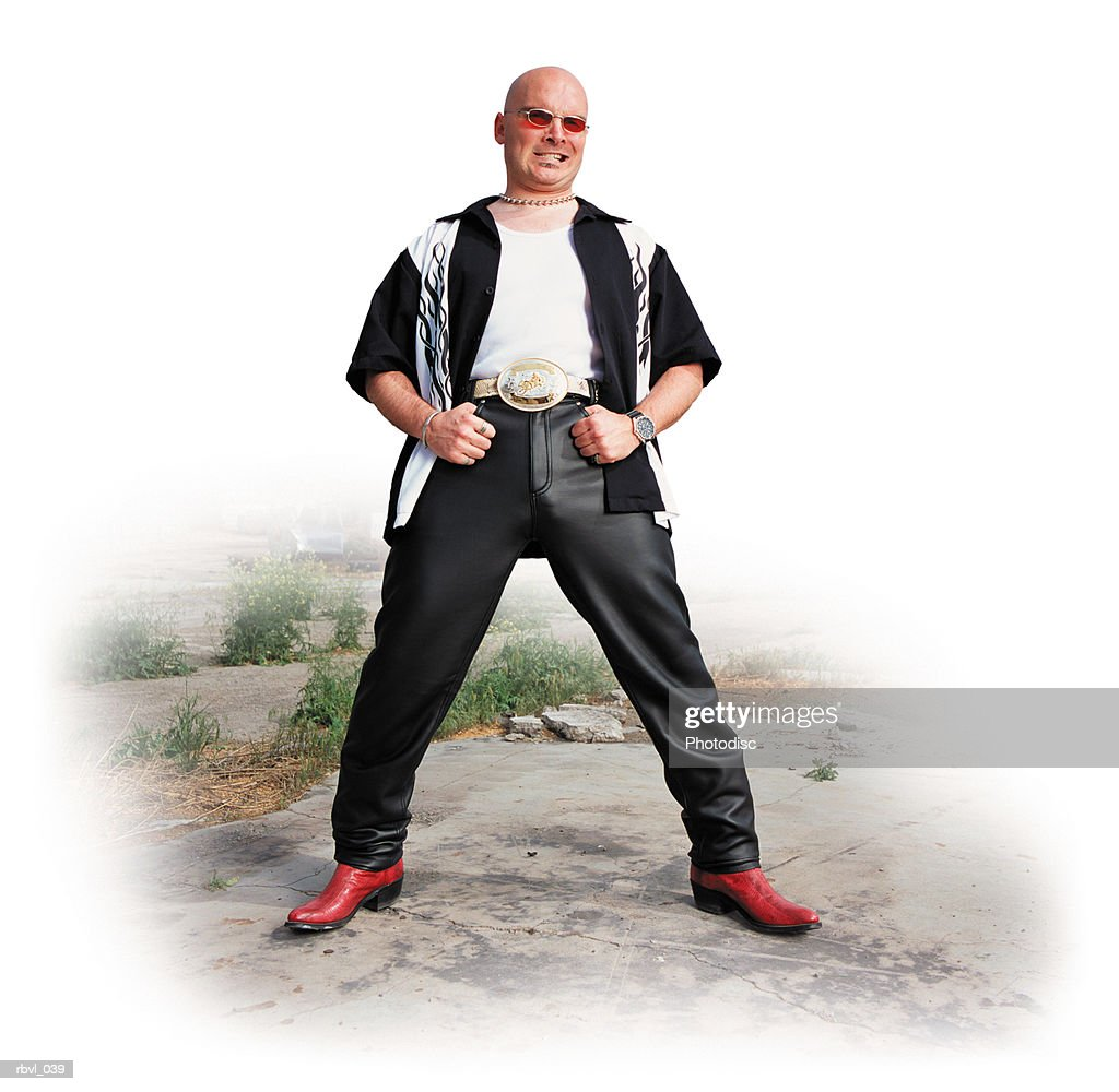 a punk bald caucasian cowboy in leather pants and red snakeskin boots with red tinted sunglasses is standing in front of an abandoned factory with a sneer on his face : Foto de stock