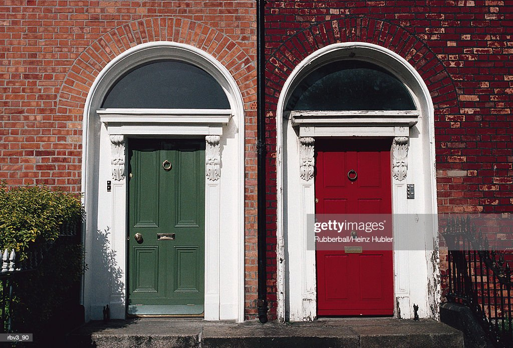 a red and green door from different houses with white frame stand next to each other with railings and green bushes present : Foto de stock