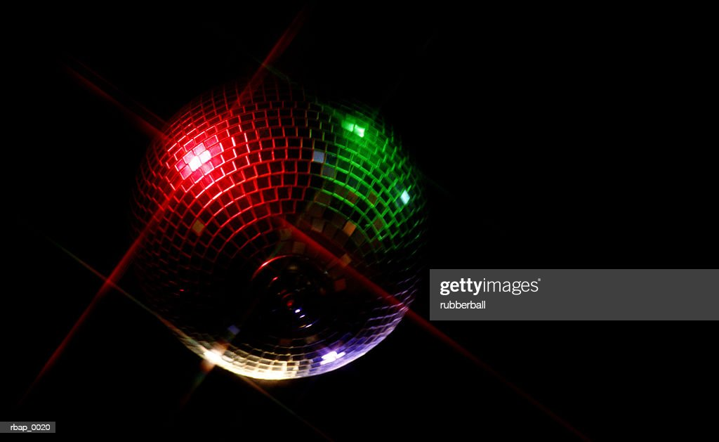 a red and green spotlighted disco ball hangs in a darkened dance room : Stockfoto