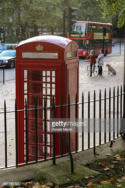 CONTENT] a red british phone booth sits new the entrance of hyde park while a double decker bus approaches in the background