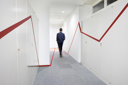 a red graphic chart on the wall and floor of the corridor, and a man walking - gettyimageskorea