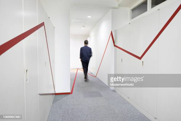 a red graphic chart on the wall and floor of the corridor, and a man walking - lineart stock-fotos und bilder
