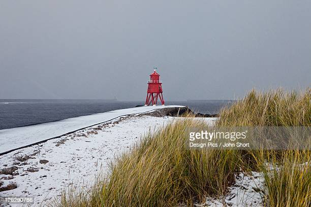 a red lighthouse along the coast under a cloudy sky in winter