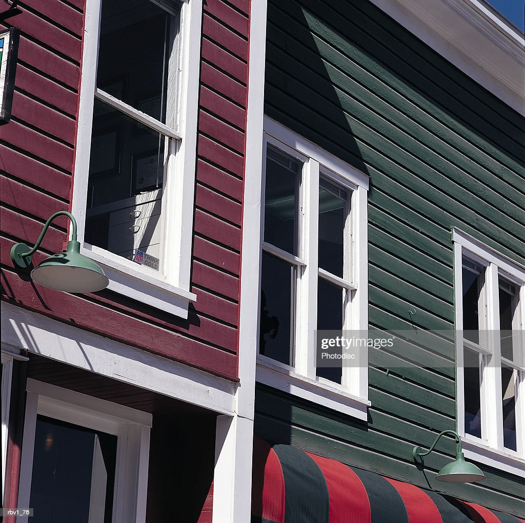 a red-violet house with white trim stands beside a green house with white trim that hold and awning under a blue sky : Foto de stock