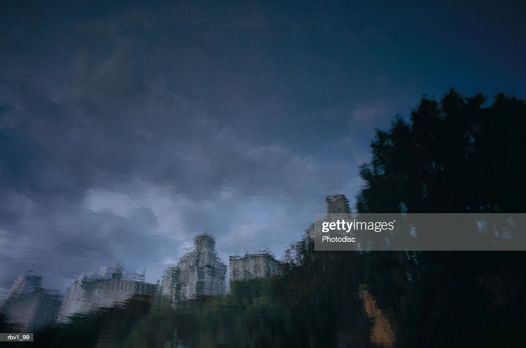 a reflection of trees and buildings with dark clouds rising above them : Foto de stock