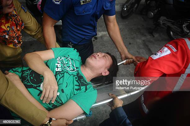 a relatives of passengers on AirAsia flight QZ 8501 is receives medical attention as he collapses at the breaking news of debris and bodies being...