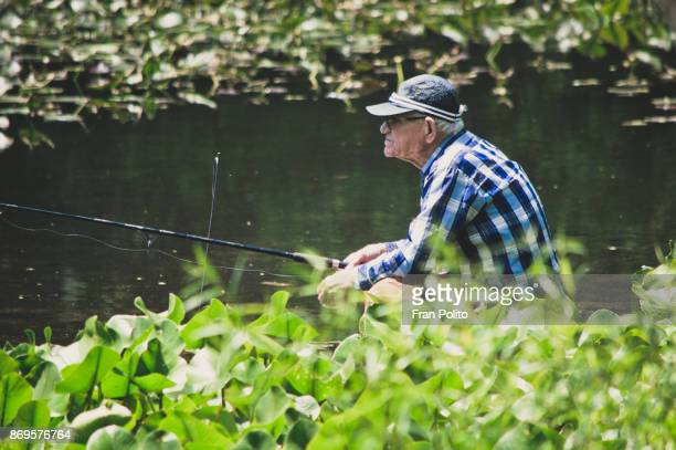a retired active senior man fishing. - baldwin brothers stock pictures, royalty-free photos & images