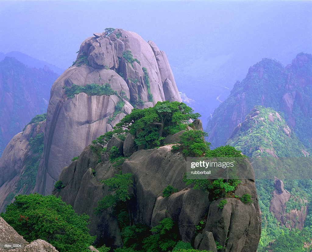 a rocky outcropping overlooks a mist-covered china mountain range : Stock Photo