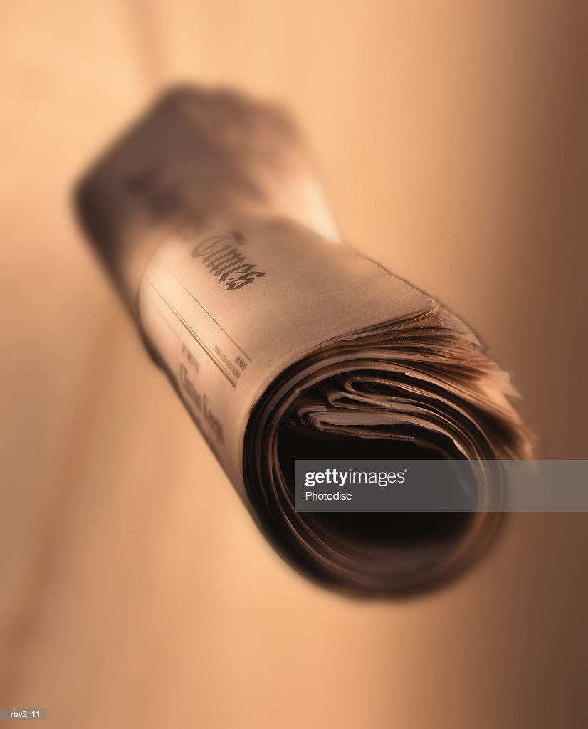 a rolled newspaper suspended in front of a brown background : Foto de stock