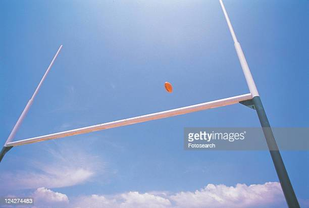 a rugby ball flying over its goal under a blue sky, low angle view - ラグビーボール ストックフォトと画像