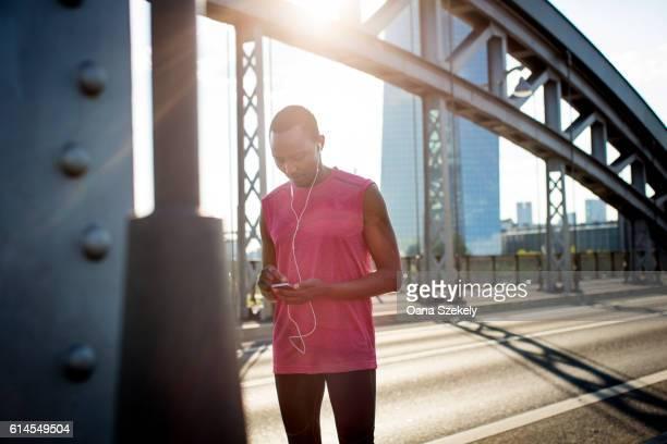 a runner in sportswear outside using a smartphone