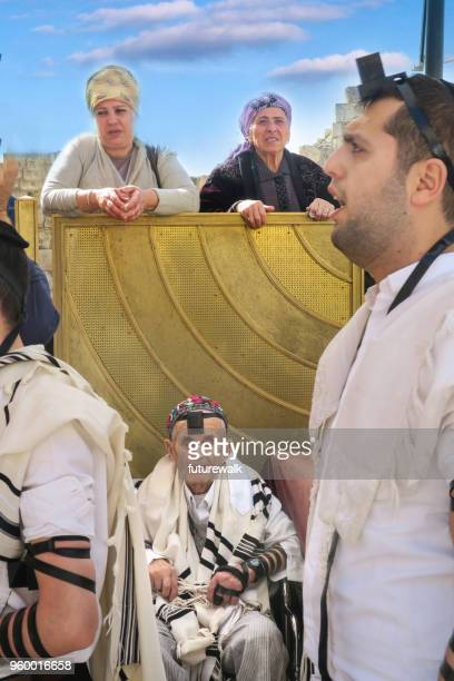 a scene at the wailing wall with men praying on the main plaza and women, who aren't allowed, watching from beyond the barrier.  jerusalem, israel, march 5, 2018 - jewish prayer shawl stock pictures, royalty-free photos & images