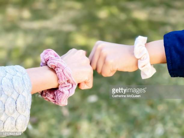 a scrunchie fist bump - social distancing stock pictures, royalty-free photos & images