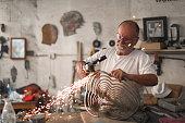 a Senior man creating sculptures in his art studio