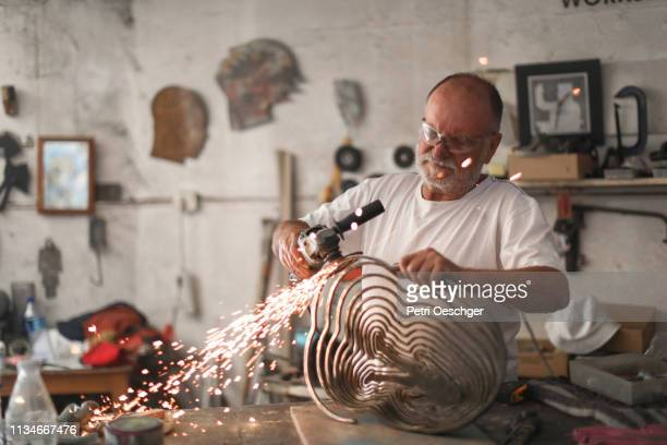 a senior man creating sculptures in his art studio - sculpture stock pictures, royalty-free photos & images