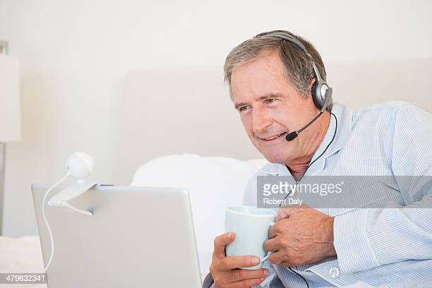 a senior man using a laptop while drinking coffee in bed