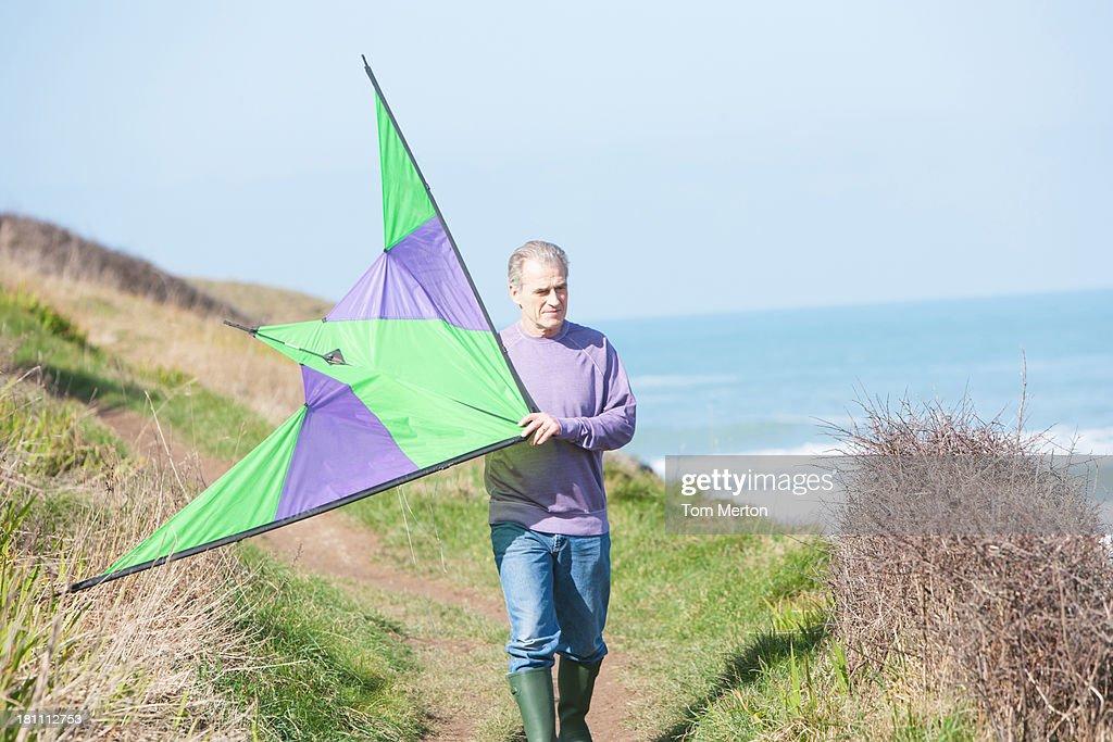 a senior man with a kite at the beach : Stock Photo