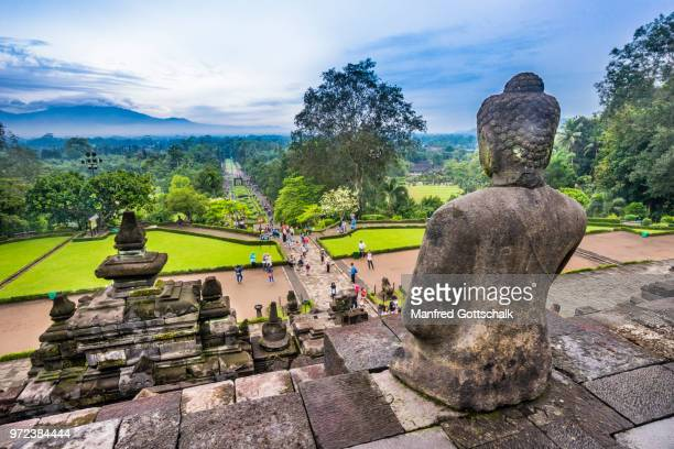 a serene sitting buddha watches on as visitor crowds make their way to the ascend of 9th century borobudur buddhist temple, central java, indonesia - java indonesia fotografías e imágenes de stock