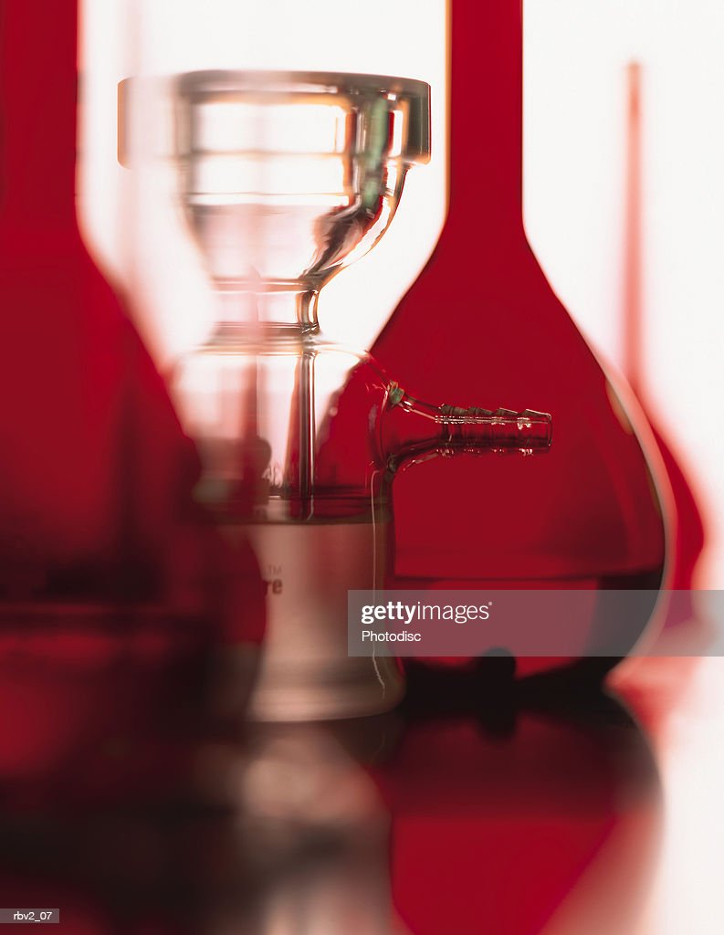 a series of red flasks and beakers stand on a shiny table with a white background : Foto de stock