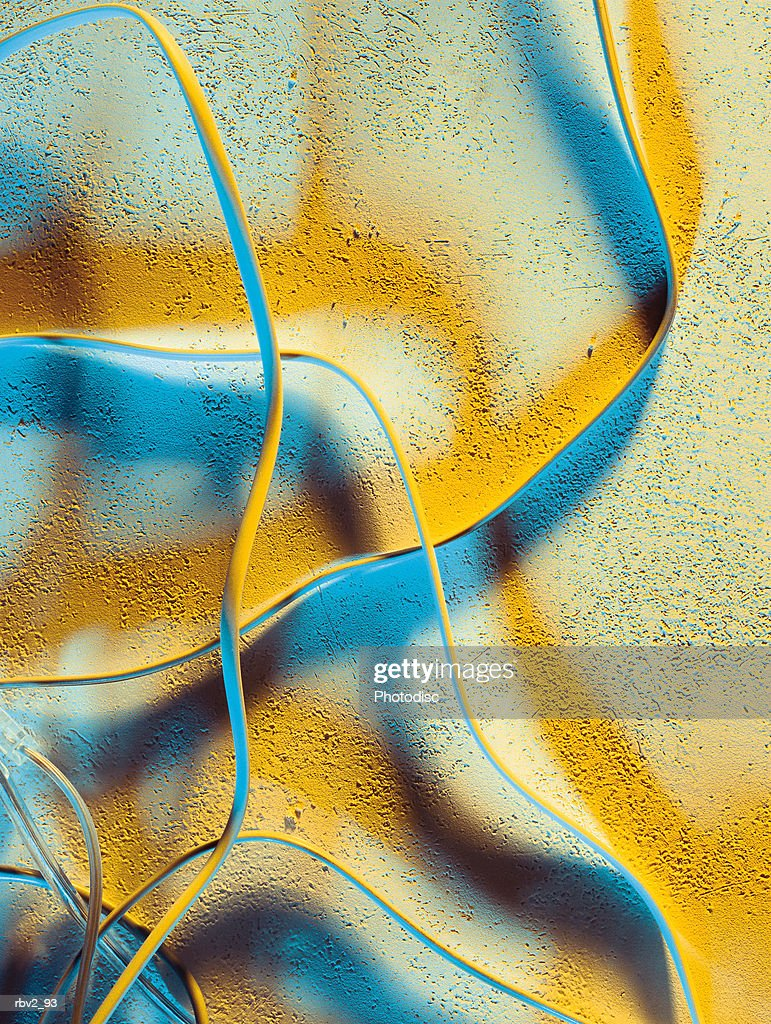 a series of white wires gives off yellow and blue shadows : Stockfoto