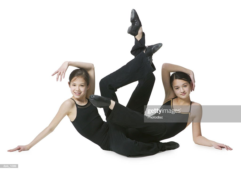 a set of young asian sisters in black leotards practice ballet poses together : Stockfoto