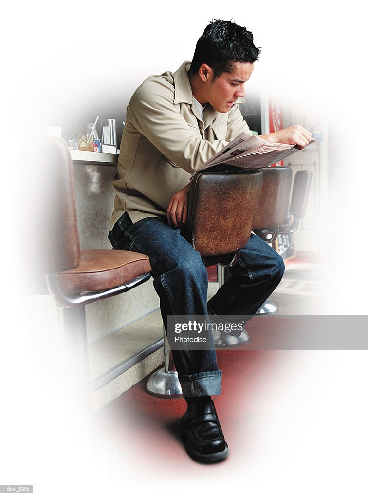 a short haired hispanic man wearing blue jeans and a tan long sleeved shirt is sitting at the counter of a diner reading a newspaper : Foto de stock