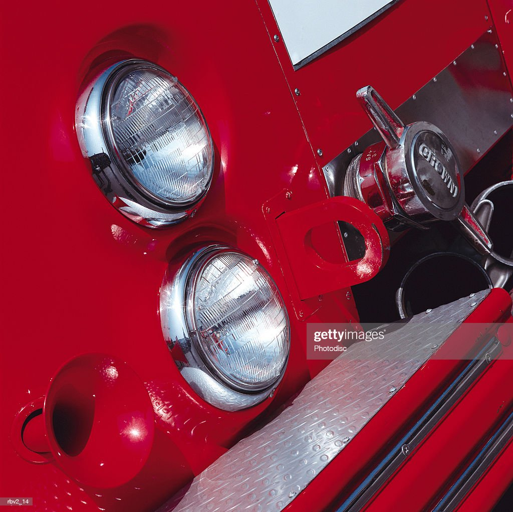 a side of a fire truck showing headlights and a horn and a water valve : Foto de stock