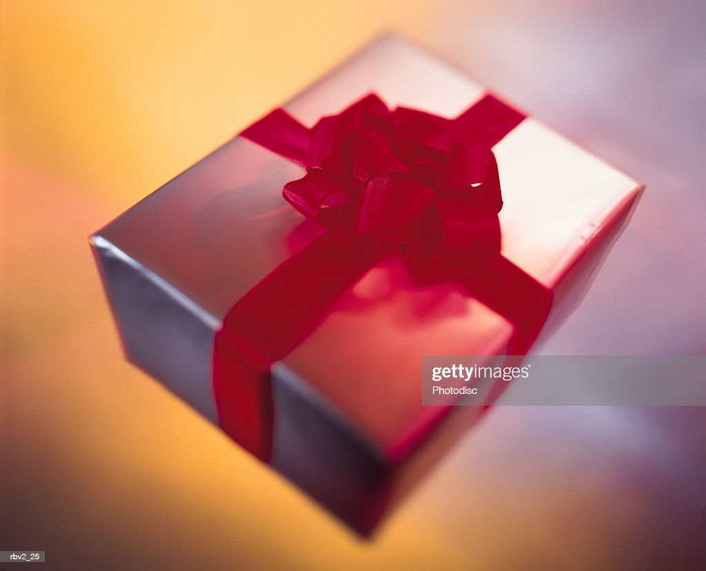 a silver and red bow wrapped gift sits on  a yellow and silver surface as light reflects off it : Foto de stock