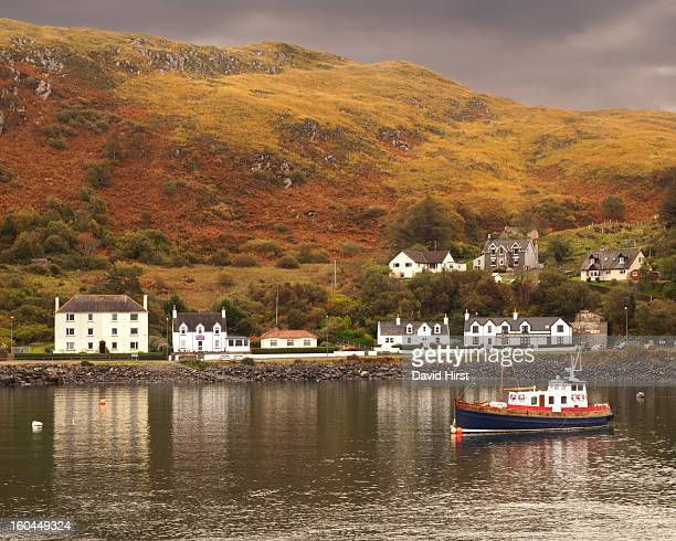 CONTENT] a small boat anchored in a calm bay at Mallaig west coast of Scotland The bay is sheltered by the highland hills and the waterside white...