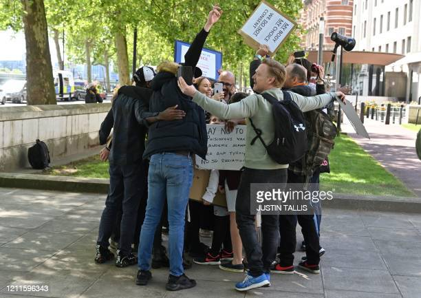 /a small group of anti-lockdown protesters have a group hug as they gather outside New Scotland Yard in Victoria, London on May 2 during the...