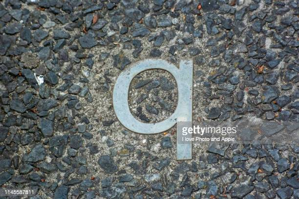 a small letter of the metal alphabet embedded in a road - letra q - fotografias e filmes do acervo