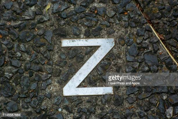 a small letter of the metal alphabet embedded in a road