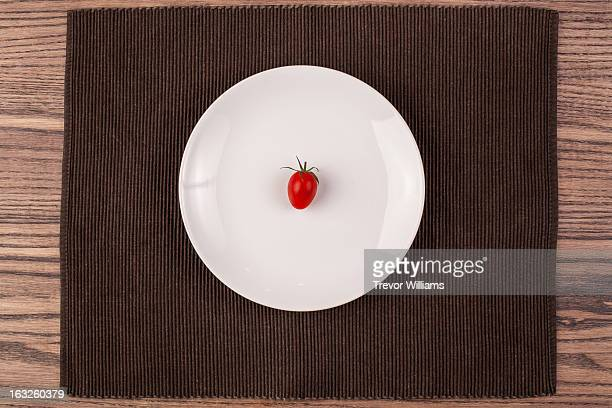 a small tomato on a plate on a wood table